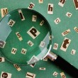 Letters cut from newspaper and magnifying glass on green background — Stock Photo #26526289