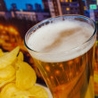 Glass of beer and potato chips in a landscape — Stock Photo #26526365
