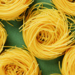 Tagliatelle pasta background on the green background — Photo