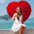 Young girl with a red umbrella sits on the waterfront and looks — Stock Photo #26526419