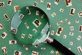 Gazete ve büyüteç camı yeşil renkli kesilmiş harfler — Stok fotoğraf