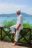 A young man in a white suit sits on the waterfront — Stock Photo