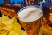 Glass of beer and potato chips in a landscape — Stock Photo