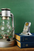Old kerosene lamp and a stack of books — Stok fotoğraf