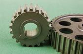Two gears on a green background — Stock Photo
