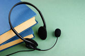 Headphones with a microphone and a stack of books on a green background — Stock Photo