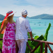 Happy young romantic couple together looking out to tropical sea — Stock Photo