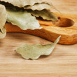 Dry bay leaf on wooden kitchen cutting board — Stock Photo #26653081