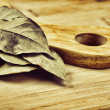 Dry bay leaf on wooden kitchen cutting board — Stock Photo #26870239