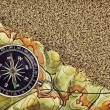 Stock Photo: Old compass on map with sand