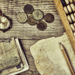 Old notes and coins and abacus on a wooden table — Stock Photo #26870321