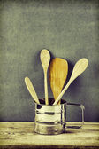 Wooden kitchenware in metal jug on old wooden table over green — Stock Photo