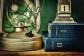 Gammal fotogenlampa och en trave böcker — Stockfoto