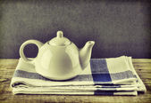 White teapot and dishcloth on old wooden table over green backgr — Stock Photo