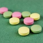 píldoras y tabletas en un fondo verde — Foto de Stock