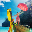 Stock Photo: Young girl standing in a wooden boat with a red umbrella in the