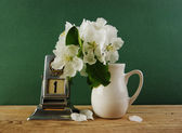 Old calendar and bird cherry branch in a jug on the wooden table — Stock Photo