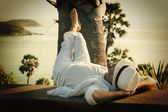 A young man in a white suit lies on the waterfront — ストック写真