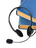 Headphones with a microphone and a stack of books isolated on wh — Stock Photo