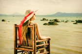 A young girl sitting on a chair and looks at the sea — Stock Photo