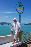 A young man in a white suit sits on the waterfront — Stok fotoğraf