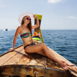 Young girl in bikini sitting on Thai Longtail boat — Stock Photo