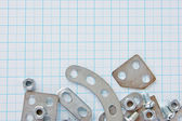 Metal parts for constructi on on graph paper — Stock Photo
