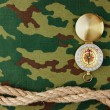 Compass and rope on a camouflage background — Stock Photo #27789703