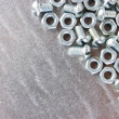 Nuts and screws on the metal plate — Stock Photo