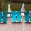 Stock Photo: Empty sun loungers by the pool