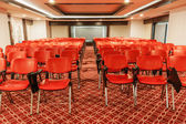 Rows of red chairs in empty conference hall — Stock Photo