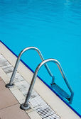 Blue swimming pool with steel ladder — Stok fotoğraf