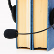 Stock Photo: Headphones with microphone and stack of books on white bac