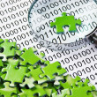 Puzzles and magnifying glass on a binary code — Stock Photo #29357293