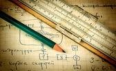 Pencil and a slide rule on the old page with the calculations in — Стоковое фото