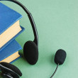 Stock Photo: Headphones with microphone and stack of books on green bac