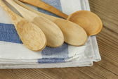 Wooden spoon and dishcloth on old wooden table — Stock Photo