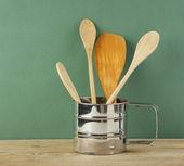 在绿色的旧木桌上的金属水罐木制厨具 — 图库照片