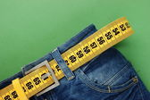 Jeans with meter belt slimming on the green background — Stock Photo