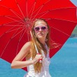 Stock Photo: Young girl with a red umbrella sits on the waterfront and looks