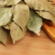 Dry bay leaf on wooden kitchen cutting board — Stock Photo #29870431