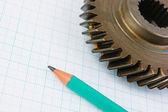 Gear and pencil on graph paper — Stock Photo