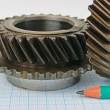 Stock Photo: Gear and pencil on graph paper