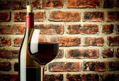 Glass of red wine and bottle in a wine cellar — Stock Photo