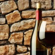 Glass of red wine and bottle in a wine cellar near the stone wall — Stock Photo