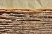 Edge of the old newspaper on a wooden background — Stock Photo