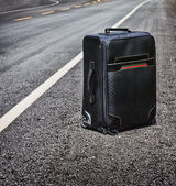 Lone suitcase stands in the middle of the road — Stock Photo