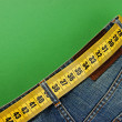 Stock Photo: Jeans with meter belt slimming on green background