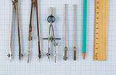 Old drawing tools on graph paper — Stock Photo