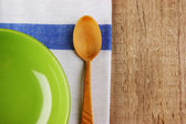 Wooden spoon with a plate on the table cloth on an old wooden ta — Stock Photo